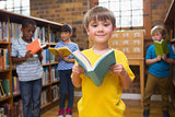 Cute pupils reading books at library