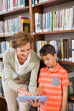 Teacher showing tablet to pupil at library