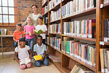Teacher and pupils smiling at camera at library