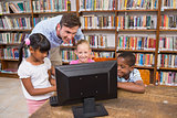 Teacher and pupils using computer at library