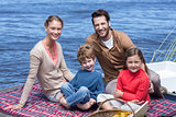 Happy family having picnic at a lake