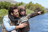 Happy casual father and son at a lake