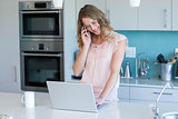 Pretty blonde on the phone using laptop