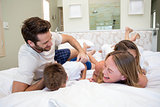 Happy family playing on the bed