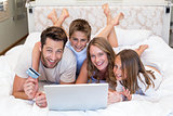 Happy family on the bed using laptop