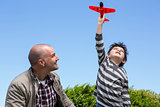Young boy playing with a toy plane
