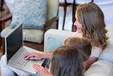 Mother and children using laptop on couch