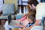 Happy family on the couch together using laptop