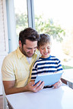 Father and son using tablet pc