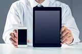 Businessman showing smartphone and tablet