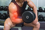 Highlighted arm of strong man lifting weights