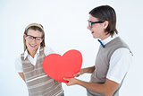 Geeky hipster offering red heart to his girlfriend