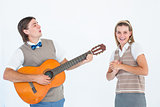Geeky hipster serenading his girlfriend with guitar