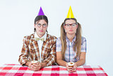 Unsmiling geeky hipsters celebrating birthday