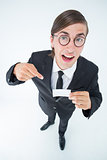 Geeky businessman looking at camera and pointing at card