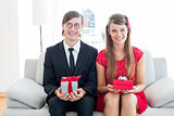 Cute geeky couple smiling and holding gift