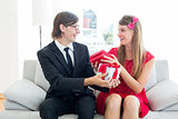 Cute geeky couple smiling and offering gift