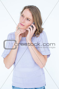 Thoughtful woman calling with her smartphone