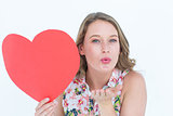 Woman holding heart card and blowing kiss