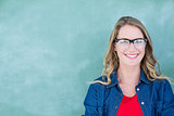 Smiling geeky teacher standing in front of blackboard