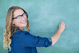 Smiling geeky teacher writing on blackboard