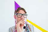 Geeky hipster wearing a party hat with blowing party horn