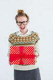 Excited geeky hipster holding present