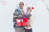 Excited geeky hipster couple looking at confetti