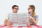 Geeky hipster couple reading newspaper