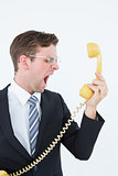 Geeky businessman shouting at telephone