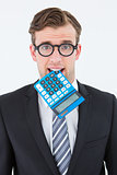 Geeky businessman biting calculator