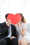Couple kissing behind heart card