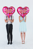 Geeky hipster couple with balloons in front of their head