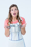 Surprised hipster woman holding pressure cooker
