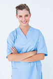 Smiling nurse in blue scrubs posing with arms crossed