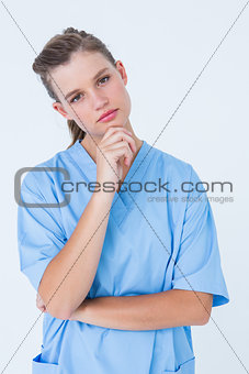 Thoughtful nurse looking at camera with hand on chin