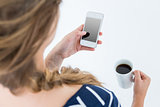 Woman using smartphone and holding mug