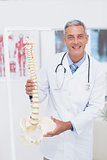 Happy doctor showing anatomical spine