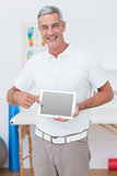 Smiling doctor showing laptop pc