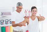 Doctor stretching a young man arm with thumb up