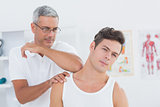 Doctor stretching a young man neck