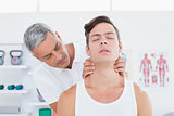 Doctor massaging a young man neck