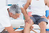 Doctor examining his patient knee