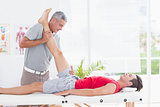 Physiotherapist doing leg stretching to his patient