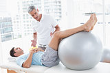 Therapist helping his patient with exercise ball