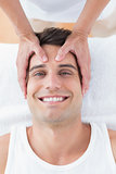 Smiling man receiving head massage