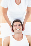 Smiling man receiving neck massage