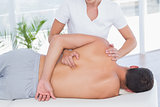 Physiotherapist doing back massage to her patient