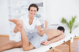 Physiotherapist doing leg massage and smiling at camera