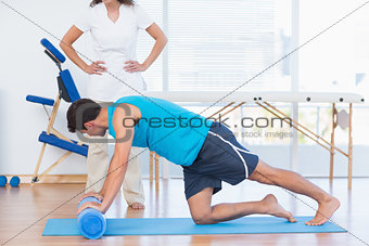 Trainer working with man on exercise mat